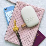 Lys grå ToCharge powerbank vist sammen med rosa taske og nøgler