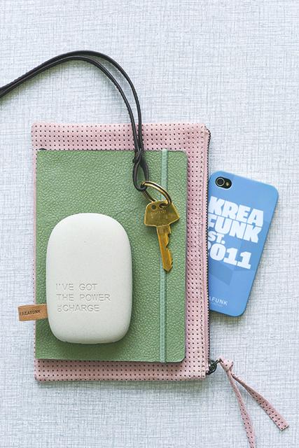 Lys grå ToCharge powerbank vist sammen med notesbøger og nøgler