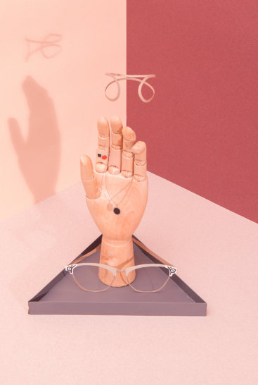 Smykkeholder-grå-hånd-på-pink-baggrund