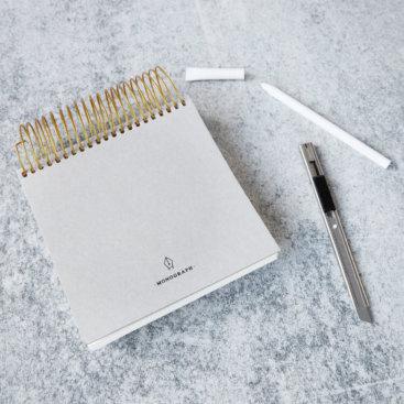 Laekker-monograph-notesblok-paa-bord